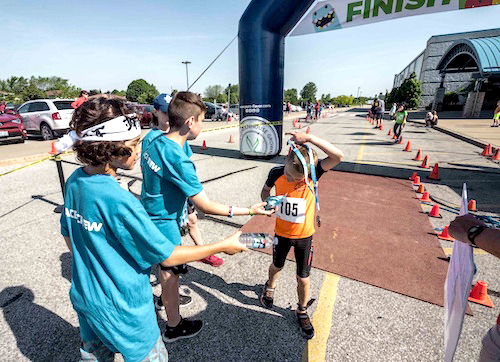 Participants greet each other at the finish line with congratulations and water.